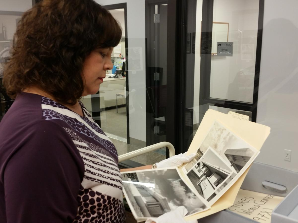 iSchool PMC Alumna Lou Kramer sorts through Wolfsom archive photographs.