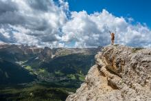 person at the top edge of a cliff celebrating their accomplishment