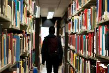 Photo of person wearing backpack walking between bookshelves