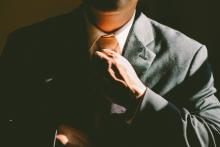 photo of person in a suit straightening neck tie