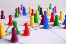 photograph of game pieces on a white lined surface to indicate strategy and network