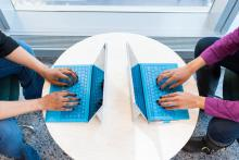 overhead photo of two women typing on laptops