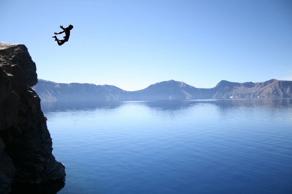 photograph of a person jumping off a cliff into Crater Lake