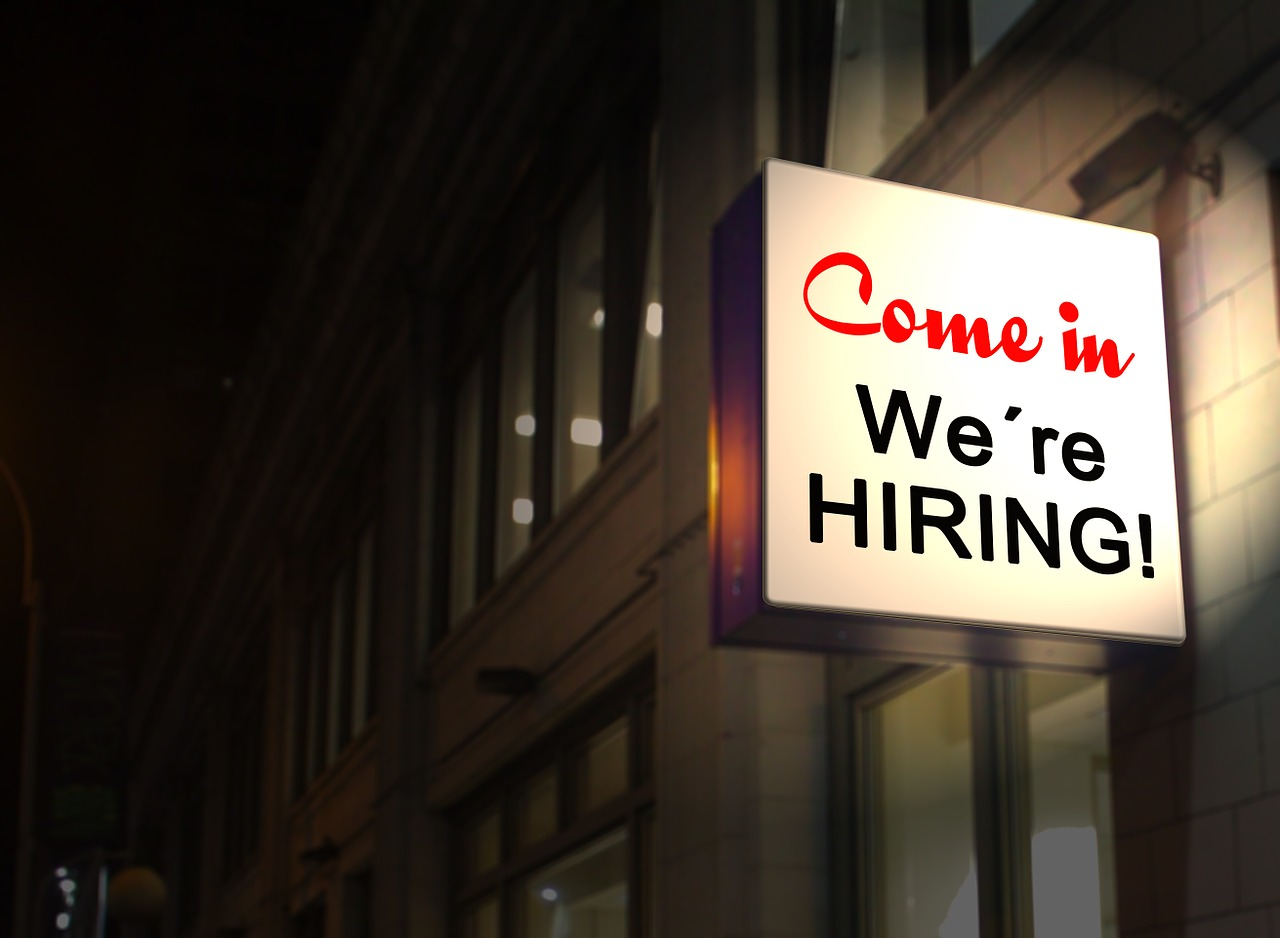 photo of a building with a sign that reads, come in we're hiring
