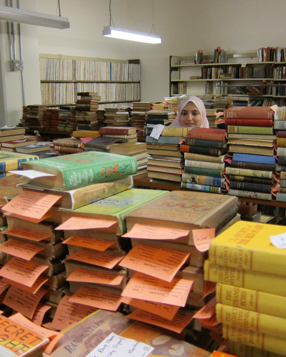 iSchool student Essraa Nawar sorts books at Leatherby library.