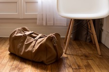 photo of a packed duffle bag sitting on the floor next to a chair