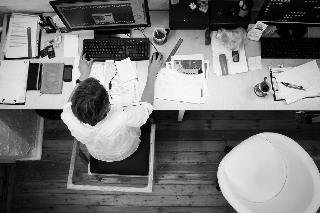 black and white overhead photo of a person working at a computer and desk covered with papers