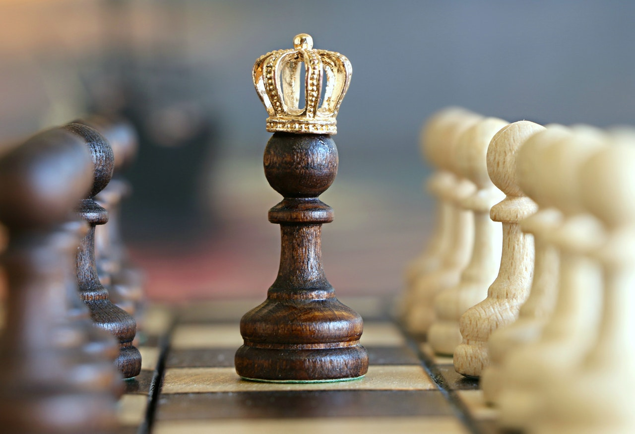 photo of a chess piece with a gold crown on top