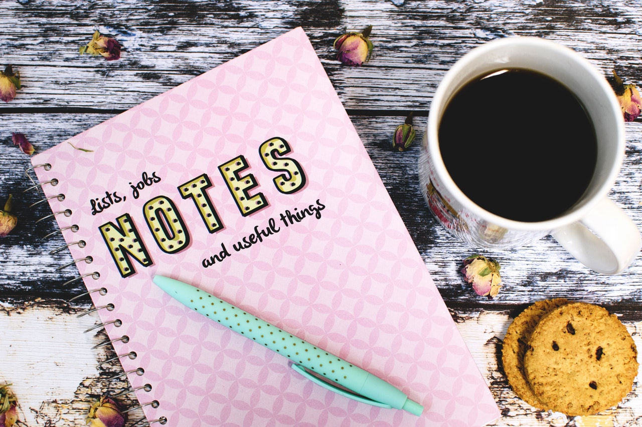photo of a taletop with coffee, cookies, a pen, and a notebook that reads: Lists, jobs, notes, and useful things