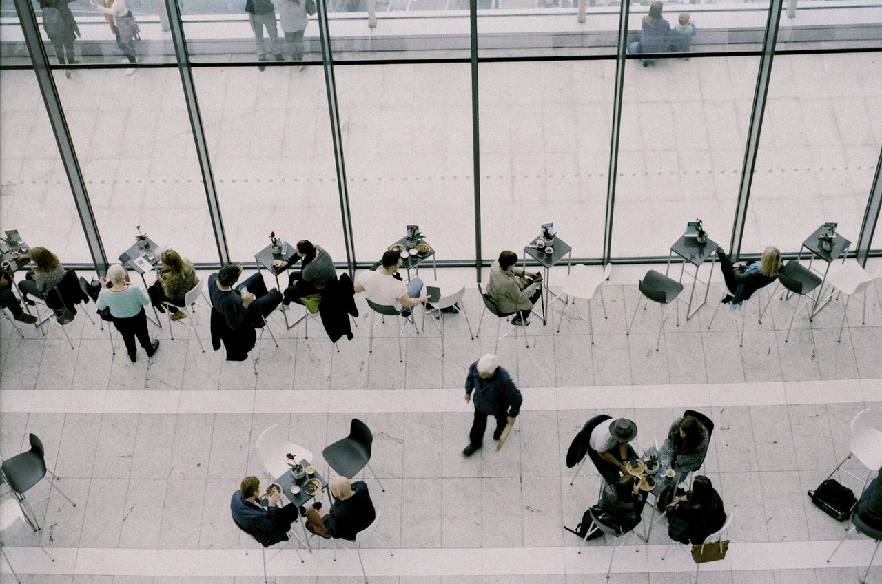 overhead photo of people talking, eating, and working at tables