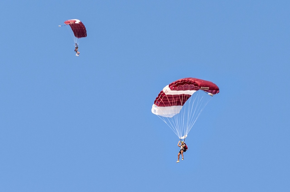 2 people sky diving with red and white parachutes