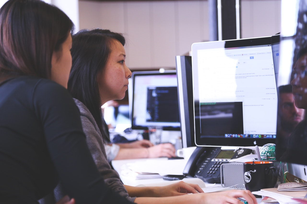 photo of two women working together at a computer
