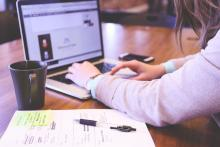 photo of person working on laptop with a mug and handwritten notes beside her