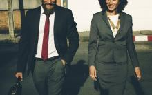 photo of two pople in business attire walking together